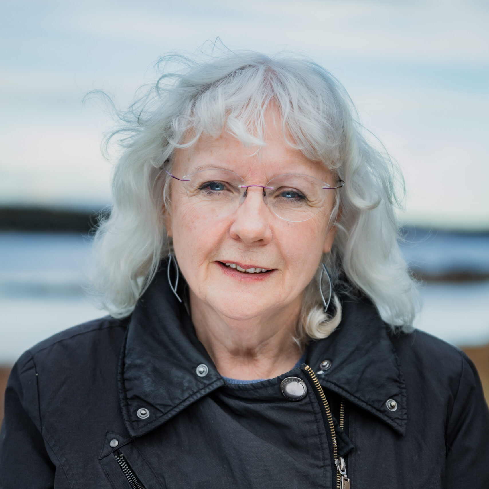 Catherine Banks, a white woman with chin length light grey hair, smiles slightly centre frame. Behind her is the ocean at early dusk.