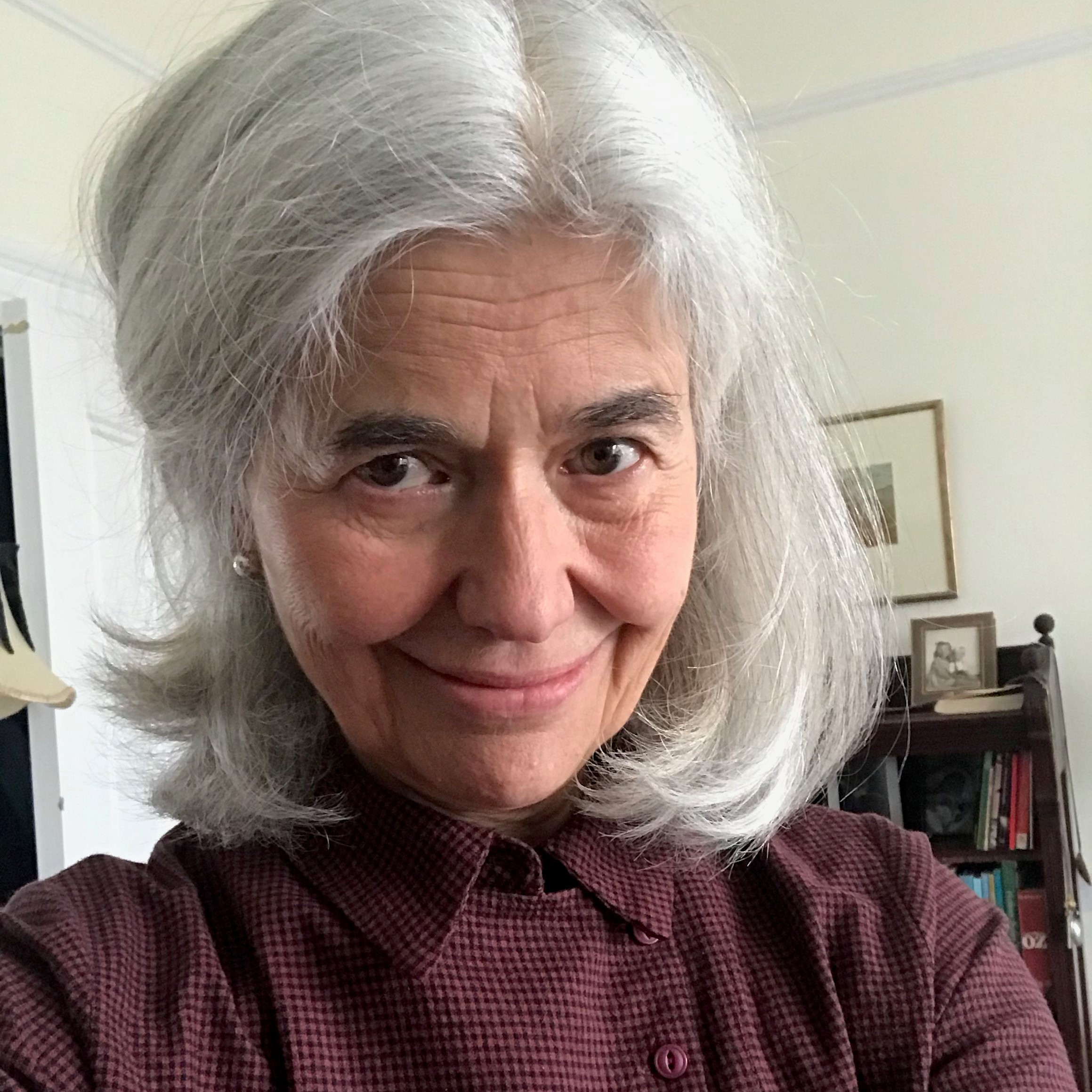 Mary Evans, a white woman with shoulder length grey hair, is smiling centre frame. Behind her is a bookcase and picture frame.