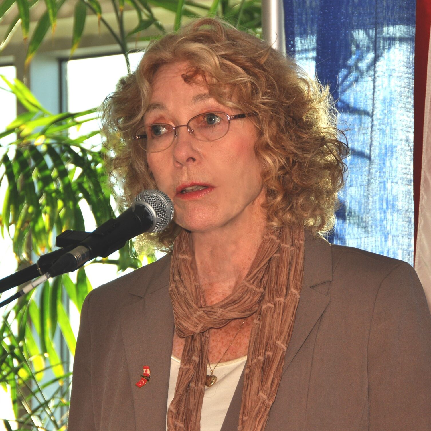 Wendy Lill, a white woman with light blonde curly hair, stands centre frame. She is speaking into a microphone and behind her are leaves from a plant.